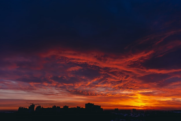 Fiery red blood vampire dawn. amazing warm dramatic fire blue dark cloudy sky. orange sunlight. atmospheric background of sunrise in overcast weather. hard cloudiness. storm clouds warning. copyspace