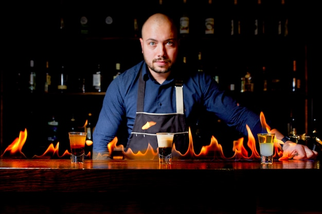 Fiery show at the bar. the bartender makes hot alcoholic cocktail and ignites bar. bartender prepares a fiery cocktail. fire on bar.