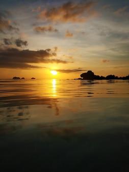 海のそばの雲と燃えるような夕日