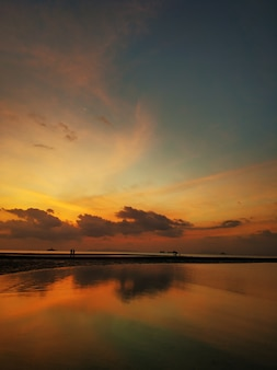海のそばの雲と燃えるような夕日。