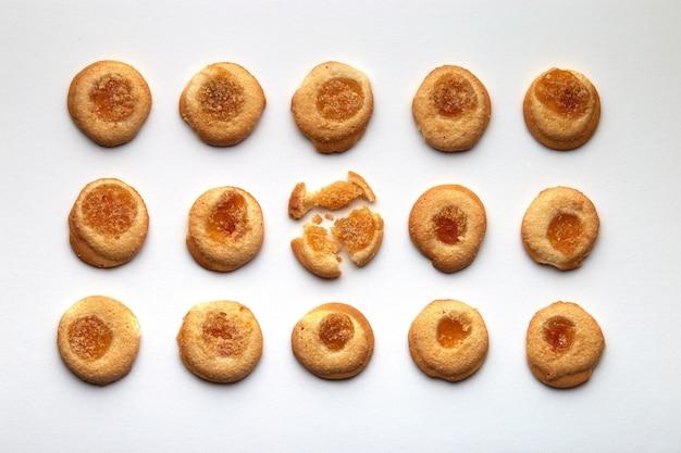 살구 잼이 균등하게 배열 된 15 개의 수제 쿠키. 흰색 배경에 고립