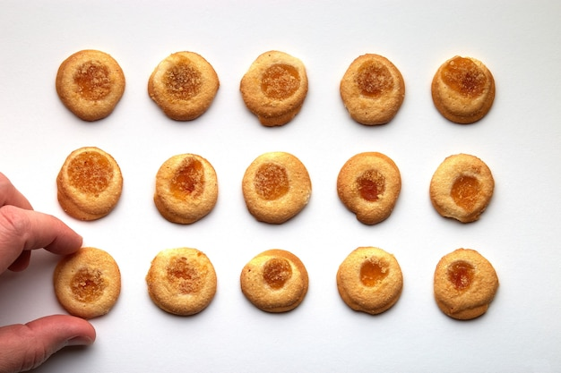 살구 잼이 균등하게 배열 된 15 개의 수제 쿠키. 맨 손은 측면에서 하나를 가져옵니다. 흰색 배경에 고립