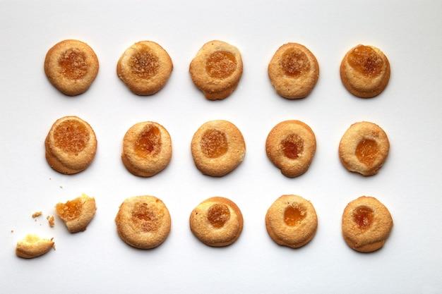 살구 잼이 균등하게 배열 된 15 개의 수제 쿠키. 구석에있는 하나가 고장났습니다. 흰색 배경에 고립