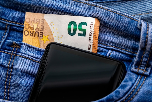 Fifty euro banknote and smartphone in blue jeans pocket. money for travel and shopping