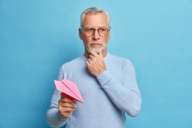 Fifty years old man holds chin and concentrated away thoughtfully makes great plans for future throws paper plane wears casual jumper and eyewear isolated over blue wall thinks about question
