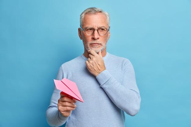 Un uomo di cinquant'anni tiene il mento e concentrato pensieroso fa grandi progetti per lanci futuri aeroplano di carta indossa un maglione casual e occhiali isolati sopra il muro blu pensa alla domanda