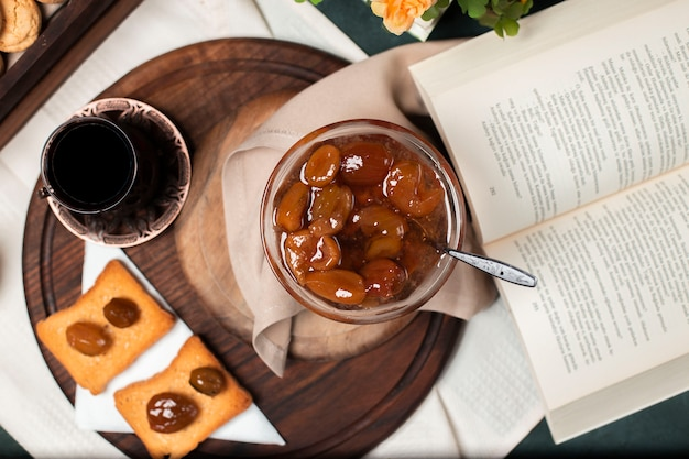 Fig confiture with a glass of black tea and some bread toasts on the wooden board.