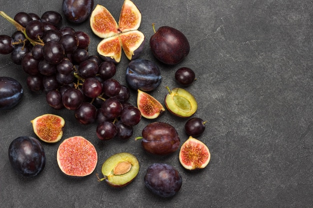 Плоды инжира и сливы на деревянной доске