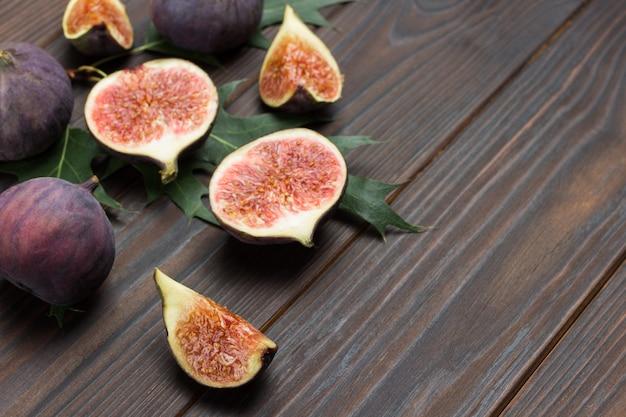Плоды инжира на деревянных фоне. половинки, четвертинки и целые плоды инжира. вид сверху. копировать пространство