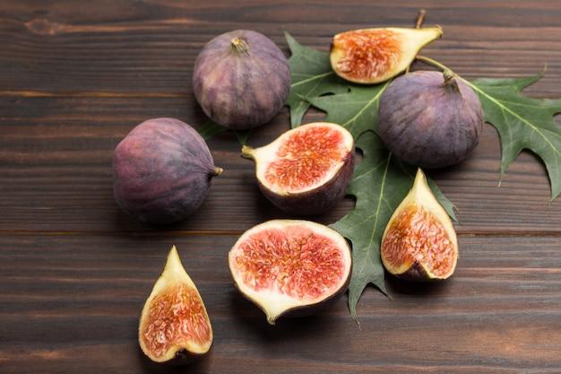 Плоды инжира на деревянной поверхности. половинки, четвертинки и целые плоды инжира. вид сверху