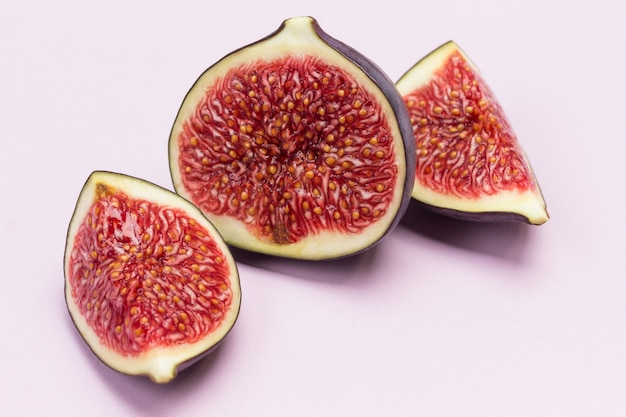 イチジクの半分。熟した果肉。閉じる。ピンクの背景。