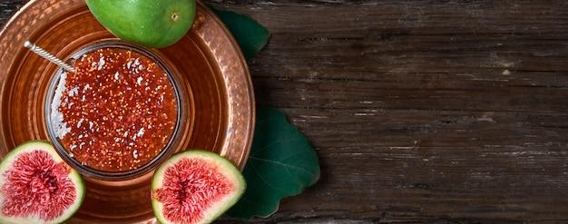 新鮮なイチジクの半分とその隣にイチジクの葉が付いている、銅のトルコ料理のガラス瓶のイチジクジャム