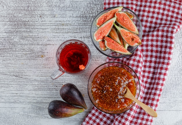 Fig jam with cup of tea, figs in a bowl on grungy and kitchen towel, top view.