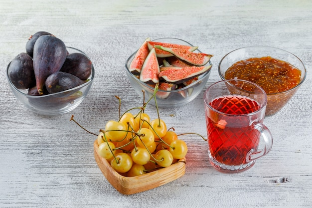 Fig jam with figs, cherries, herbal tea in a bowl on grungy, high angle view.