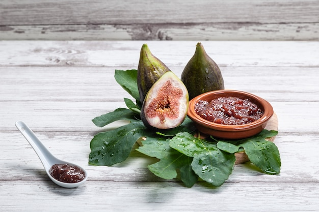 Fig jam with figs, fig leaves and white spoon with jam