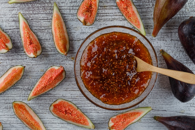 Fig jam with figs, spoon in a bowl on grungy, flat lay.