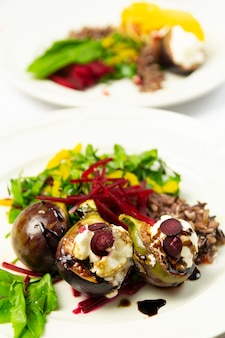 Fig salad with goat cheese and beets, on two white plates