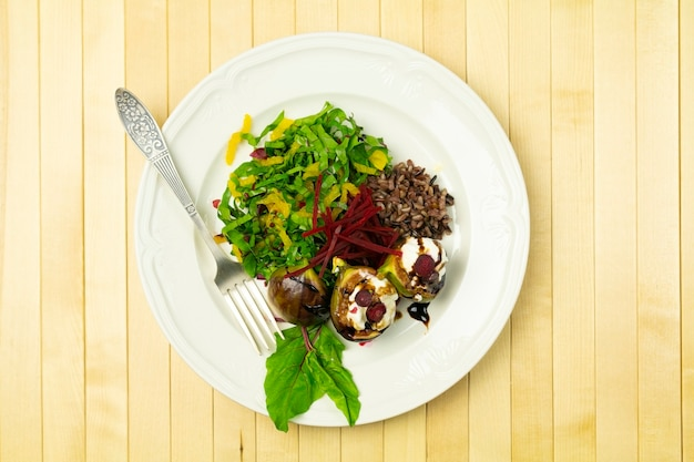 Fig salad with goat cheese and beets, on a white plate on a checkered tablecloth, wooden table, top view