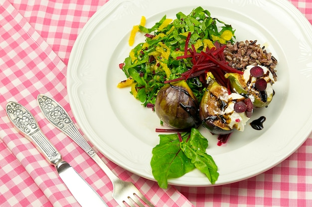 Fig salad with goat cheese and beets, on a white plate on a checkered tablecloth