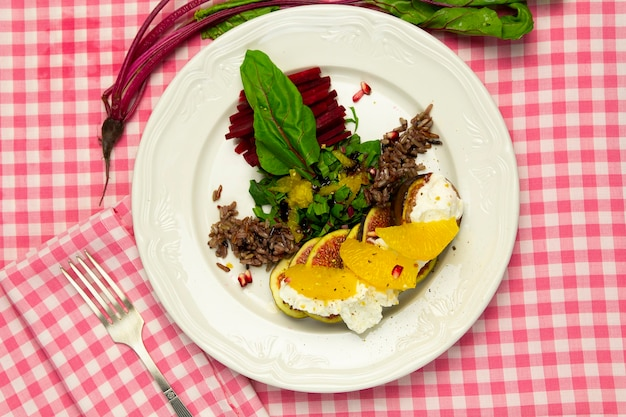 Fig salad with goat cheese and beets, on a white plate and fork, top view