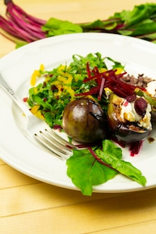 Fig salad with goat cheese and beets, on a white plate and fork