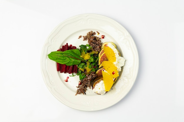 Fig salad with goat cheese and beets, on a white plate, top view