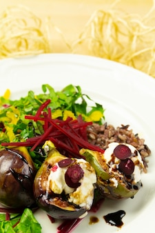 Fig salad with goat cheese and beets, on a white plate