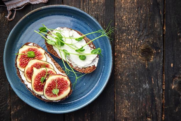 イチジクサンドイッチクリームチーズヘルシーな朝食新鮮な部分テーブルで食事スナックを食べる準備ができて