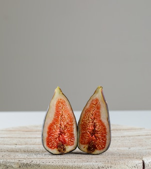 Fig slices on wooden board on white and grey, side view.