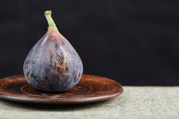 A fig on small plate and on marble table.