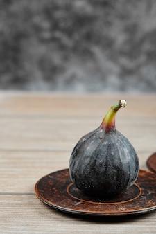 Un fico sul piatto piccolo e sul tavolo di legno.