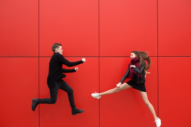 Fight in jump. a man and a woman on a red background.