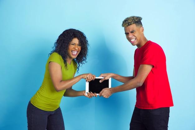 Combatti per il tablet per divertimento. giovane uomo afro-americano emotivo e donna in abiti casual colorati su sfondo blu. bella coppia. concetto di emozioni umane, espansione facciale, relazioni, annuncio.