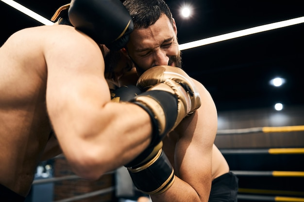 A fighter closing his eyes in pain from a strong punch