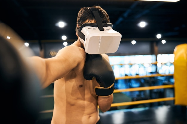 Fighter delivering a blow with virtual reality glasses on his head