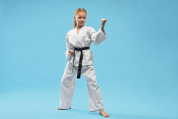 Боец в кимоно смотрит в сторону и борется в студии