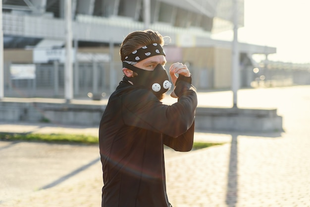 Человек-истребитель, тренирующий боксерский удар на городской улице, портрет фитнес-мужчины, боксирующего на открытом воздухе в черном