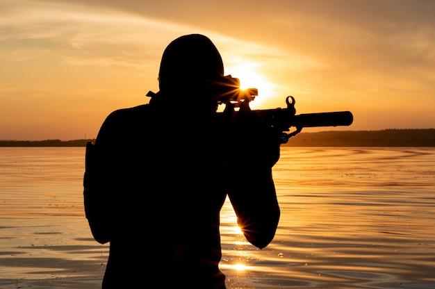 Боец спецподразделения выходит из воды и готовится к началу операции. смешанная техника. понятие нестабильности в мире, боевых действий, кризиса. россия против сша