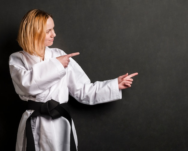 Fighter woman pointing at copy space