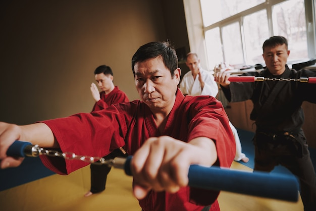 Fighters in different colors keikogi training with nunchuck.