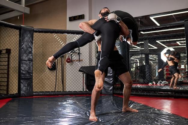 Mmaボクサーのファイターはジムのケージリングでルールなしで戦っています。チャンピオンシップの準備をしているリングのmmaファイター。ルールのないボクシングの戦い