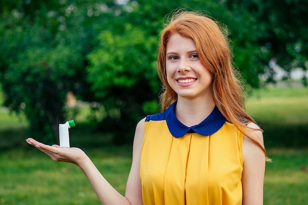 Fighting asthma and bronchitis. active cheerful beautiful young ginger redhead irish norwegian woman in a yellow dress holding the inhaler in the hand in the summer park . concept of spring allergy