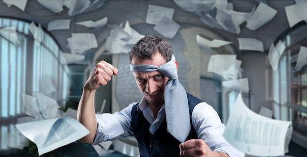 Боевой бизнесмен с галстуком на голове в офисе