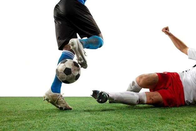 戦い。白い壁に隔離されたフィールドでボールのために戦うプロサッカー、サッカー選手の足を閉じます。ゲーム中のアクション、モーション、緊張感のある感情の概念。トリミングされた画像。