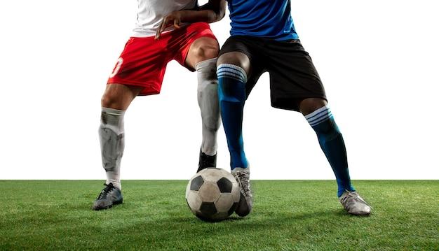 Боевые действия. закройте ноги профессионального футбола, футболистов, борющихся за мяч на поле, изолированном на белой стене. концепция действия, движения, сильных эмоций во время игры. обрезанное изображение.