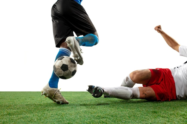 Fighting. close up legs of professional soccer, football players fighting for ball on field isolated on white wall. concept of action, motion, high tensioned emotion during game. cropped image.