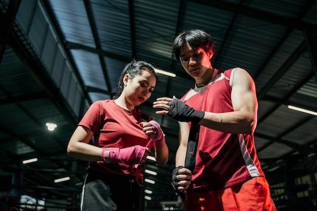 싸우는 부부 준비. 그녀의 손을 감싸는 찢어진 아시아 남성과 여성 전투기의 자른 샷