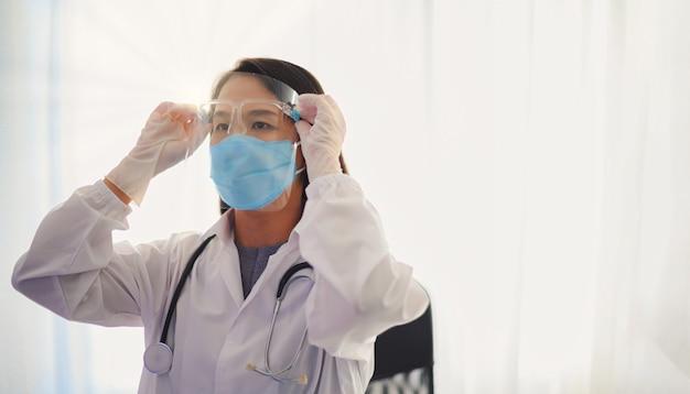 Доктор готовится к хирургической операции и надевает защитные очки для fighting covid-19