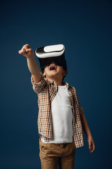 Fighting the fake world. little boy or child in jeans and shirt with virtual reality headset glasses isolated on blue studio background. concept of cutting edge technology, video games, innovation.