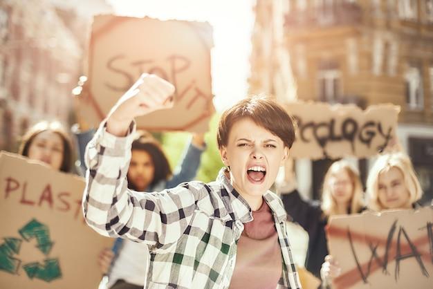 깨끗한 지구를 위해 싸우는 젊고 강한 여성은 한 그룹과 함께 생태를 위해 항의하고 있습니다